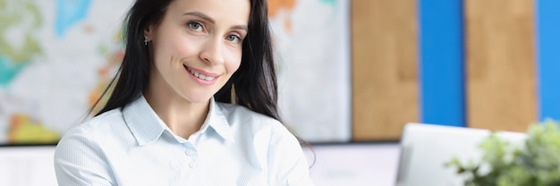 Jonge lachende zakenvrouw zit op laptop in kantoor
