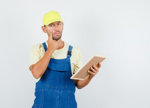 Jonge lader in uniform bedrijf bord met vinger op wang en op zoek triest, vooraanzicht.