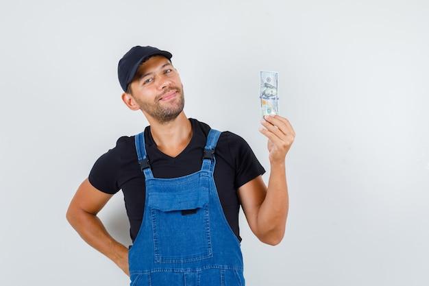 Jonge lader in uniform met dollarbiljet en op zoek vrolijk, vooraanzicht.