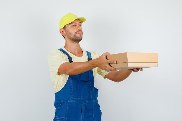 Jonge lader levert kartonnen doos in uniform, vooraanzicht.