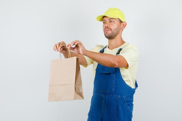 Jonge lader levert papieren zak in uniform en kijkt voorzichtig, vooraanzicht.