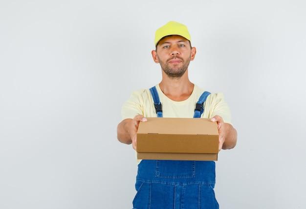 Jonge lader overhandigen kartonnen doos in uniform, vooraanzicht.