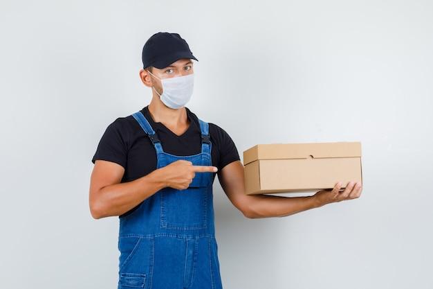 Jonge lader wijzend op kartonnen doos in uniform, masker vooraanzicht.