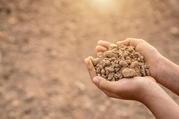 Jonge landbouwer die droge grond in leeg land voor het planten houdt