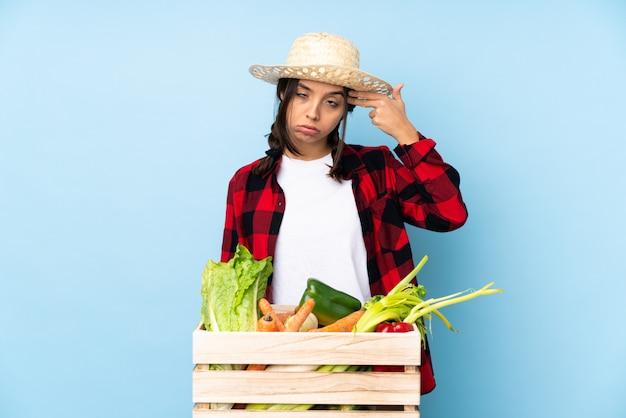Jonge landbouwer vrouw die verse groenten in een houten mand met problemen houdt die zelfmoordgebaar maken