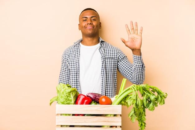 Jonge landbouwersmens die op beige glimlachend vrolijk wordt geïsoleerdt die nummer vijf met vingers toont.
