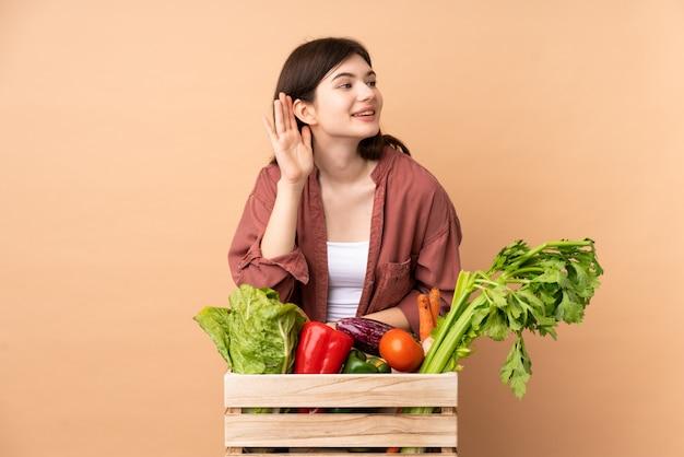Jonge landbouwersvrouw met vers geplukte groenten in een doos die aan iets luisteren door hand op het oor te zetten