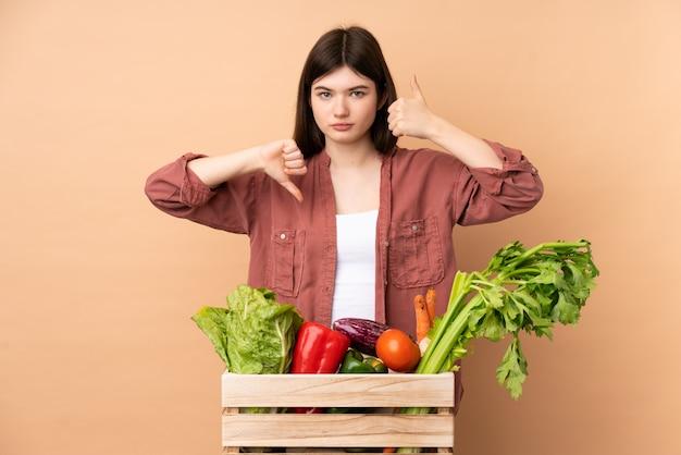 Jonge landbouwersvrouw met vers geplukte groenten in een doos die goed-slecht teken maakt. onbeslist tussen ja of niet