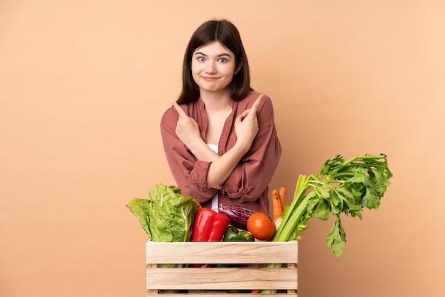 Jonge landbouwersvrouw met vers geplukte groenten in een doos die naar de zijtakken wijzen die twijfels hebben