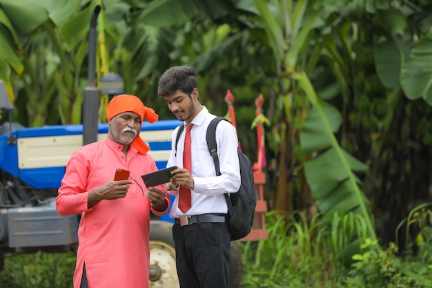 Jonge landbouwingenieur die aan landbouwer wat informatie in slimme telefoon toont