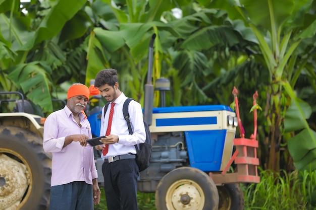 Jonge landbouwingenieur die wat informatie in tablet toont aan indische landbouwer