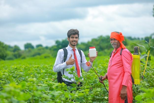 Jonge landbouwingenieur met landbouwer die kunstmest botle in veld toont