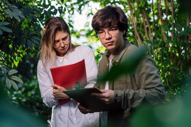 Jonge landbouwingenieurs die in serre werken