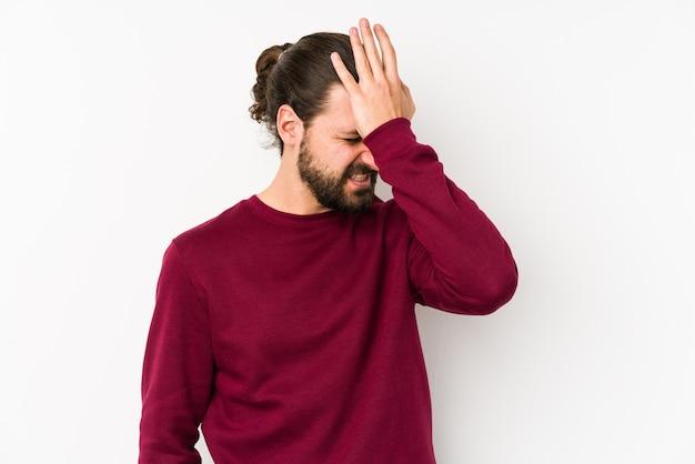 Jonge lange haarmens die op een witte muur wordt geïsoleerd die iets vergeet, voorhoofd met handpalm slaat en ogen sluit.