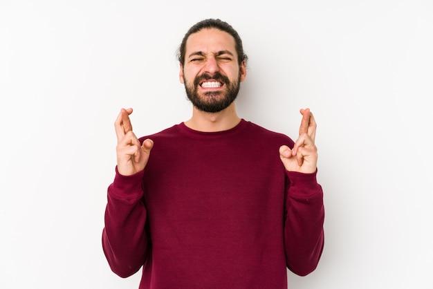 Jonge lange haarmens op een witte muur die vingers kruist
