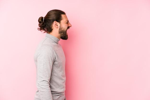 Jonge lange haren man geïsoleerd op een roze achtergrond schreeuwen naar een kopie ruimte