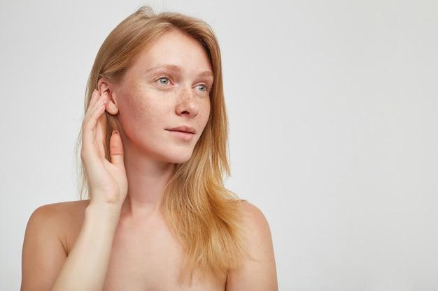 Jonge langharige aantrekkelijke dame met ongedwongen haarstijl die haar hand naar haar oog opheft en dromerig opzij kijkt terwijl ze poseren over een witte muur