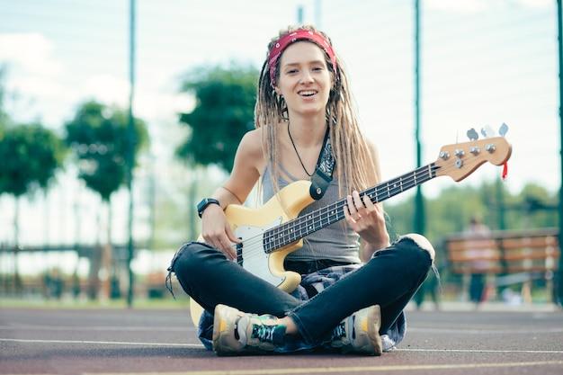 Jonge langharige dame met dreadlocks zittend met haar benen gekruist en lachend tijdens het spelen van de gitaar