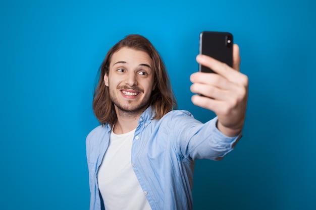 Jonge langharige man met baard lacht en maakt een selfie met behulp van een telefoon op een blauwe studiomuur in vrijetijdskleding