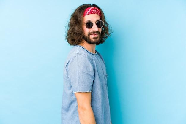 Jonge langharige man met een festival hipster kijkt geïsoleerd kijkt opzij glimlachend, vrolijk en aangenaam.