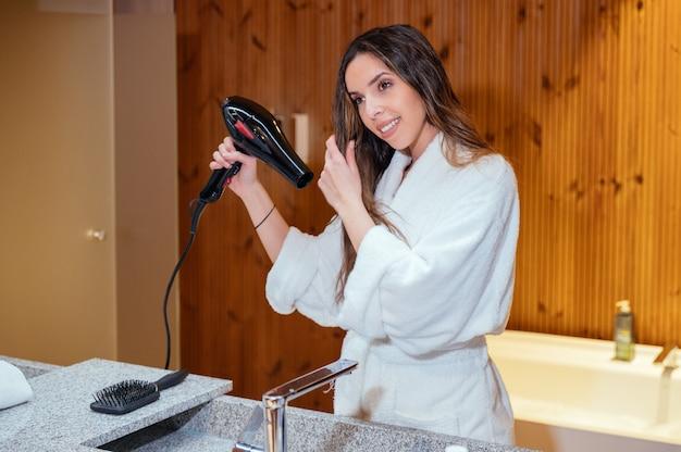 Jonge langharige vrouw in witte badjas met behulp van een föhn na het baden procedure in de badkamer