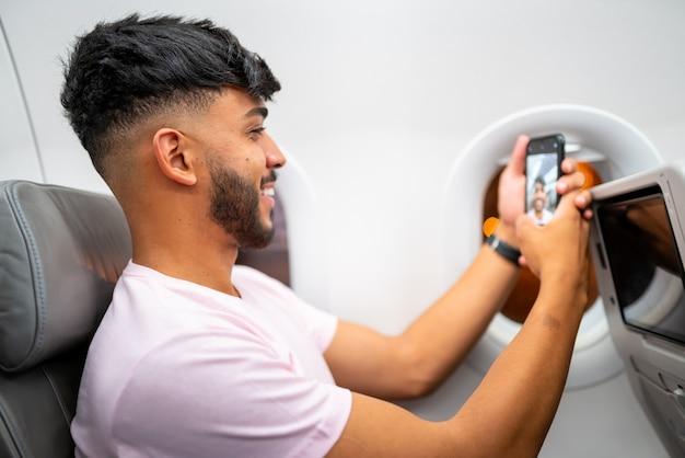 Jonge latijns-amerikaanse man die lacht tijdens een videogesprek op zijn mobiele telefoon, zittend in het vliegtuig bij het raam