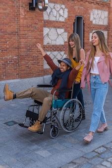 Jonge latijns-amerikaanse man in een rolstoel naast twee jonge blanke meisjes die blij en lachend door de straat slenteren