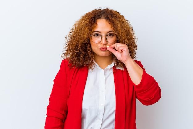 Jonge latijns-bochtige vrouw geïsoleerd op een witte achtergrond met vingers op lippen die een geheim houden.