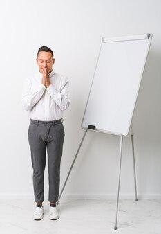 Jonge latijns-coach man met een whiteboard hand in hand bidden in de buurt van mond, voelt zich zelfverzekerd.