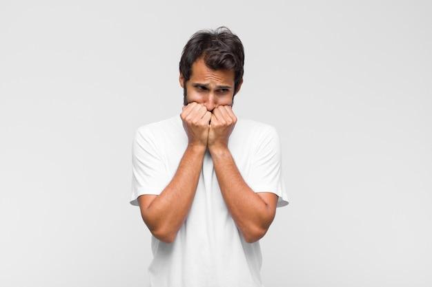 Jonge latijns-knappe man die bezorgd, angstig, gestrest en bang kijkt, vingernagels bijt en naar laterale kopie ruimte kijkt