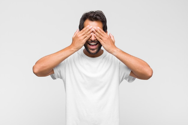 Jonge latijns-knappe man die glimlacht en zich gelukkig voelt, de ogen bedekt met beide handen en wacht op een ongelooflijke verrassing