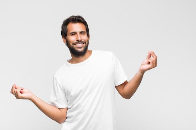 Jonge latijns-knappe man die lacht, zich onbezorgd, ontspannen en gelukkig voelt, danst en naar muziek luistert, plezier heeft op een feestje