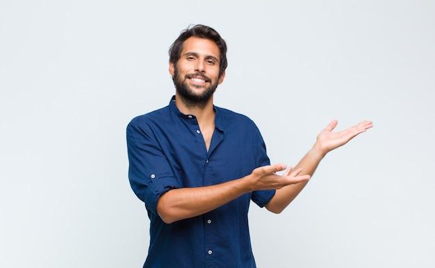 Jonge latijns-knappe man die vrolijk lacht en een warme, vriendelijke, liefdevolle welkomstknuffel geeft, zich gelukkig en schattig voelt