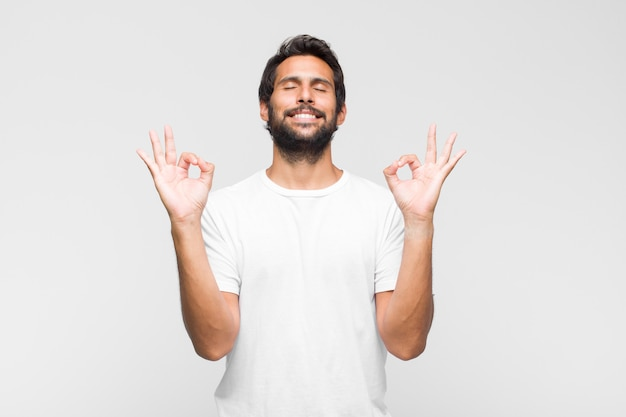 Jonge latijns-knappe man kijkt geconcentreerd en mediteert, voelt zich tevreden en ontspannen, denkt of maakt een keuze