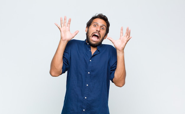 Jonge latijns-knappe man schreeuwen met de handen in de lucht, zich woedend, gefrustreerd, gestrest en boos voelen
