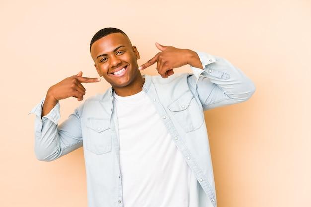 Jonge latijns-man geïsoleerd op beige muur glimlacht, wijzende vingers naar mond