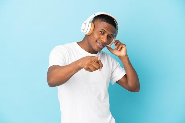 Jonge latijns-man geïsoleerd op blauwe muur luisteren muziek en wijst naar de voorkant