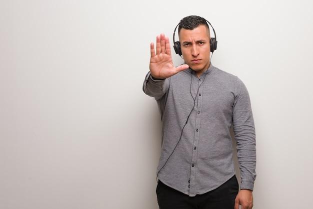 Jonge latijns-man luisteren naar muziek hand in front