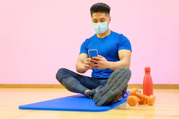 Jonge latijns-man met beschermend gezichtsmasker, ontspannen, met behulp van mobiele telefoon na training in de sportschool tijdens pandemie nieuw normaal.