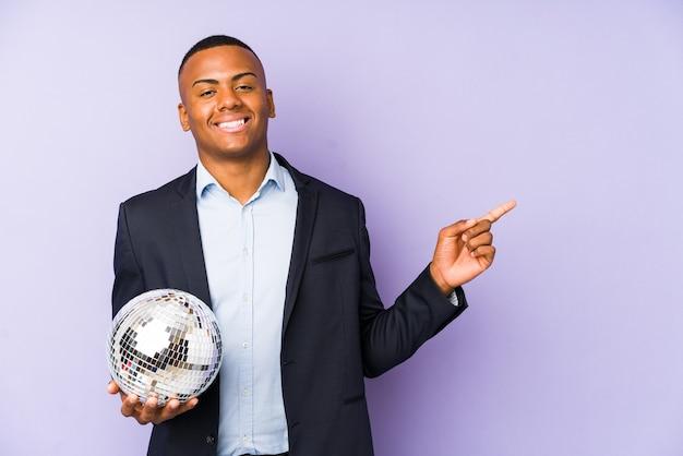 Jonge latijns-man met een bal partij geïsoleerd glimlachend en opzij wijzend, iets laten zien op lege ruimte.