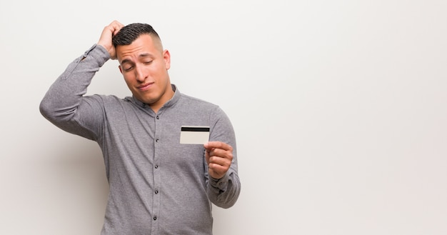 Jonge latijns-man met een creditcard bezorgd en overweldigd
