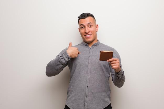 Jonge latijns-man met een portemonnee verrast, voelt zich succesvol en welvarend