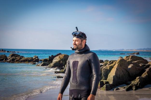 Jonge latijns-man met een wetsuit en snorkel op het rotsachtige strand starend naar de skyline