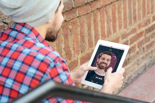 Jonge latijns-man ontgrendeling smartphone met gezichtsherkenning technologie