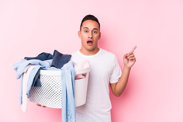 Jonge latijns-man oppakken van vuile kleren geïsoleerd wijzend naar de zijkant