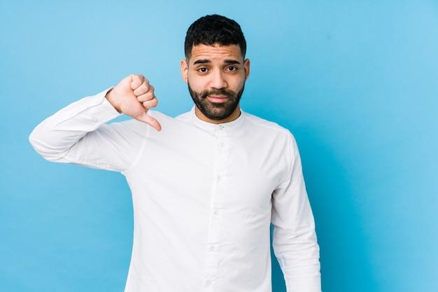 Jonge latijns-man tegen een geïsoleerd blauw met een afkeer gebaar, duimen naar beneden. meningsverschil concept.