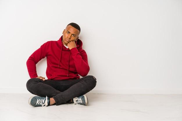 Jonge latijns-man zittend op de vloer geïsoleerd die verdrietig en peinzend voelt, kijkend naar kopie ruimte.