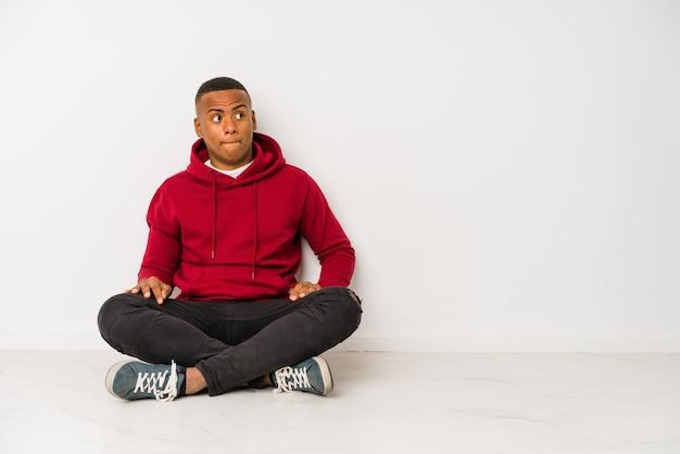 Jonge latijns-man zittend op de vloer geïsoleerd verward, voelt twijfelachtig en onzeker.
