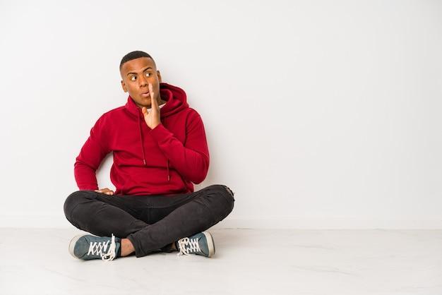 Jonge latijns-man zittend op de vloer geïsoleerd zegt een geheim heet remmend nieuws en kijkt opzij