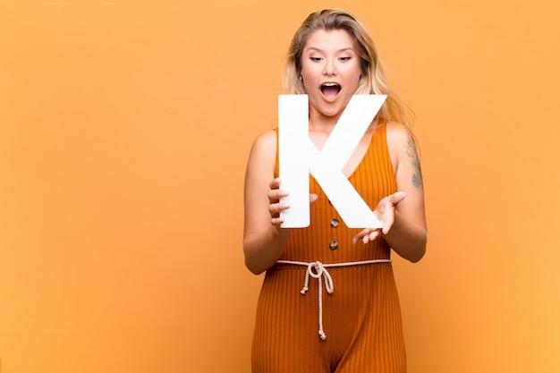 Jonge latijns-mooie vrouw verrast, geschokt, verbaasd, met de letter k van het alfabet om een woord of een zin te vormen.